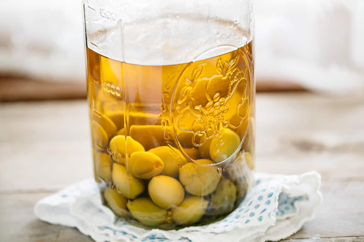 Plum wine maturing in a glass jar