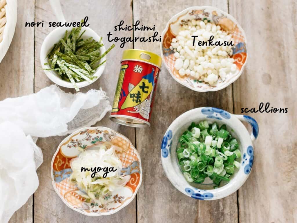 shredded nori seaweed, shichimi togarashi, tenkasu, myoga, and finely chopped scallions in small bowls