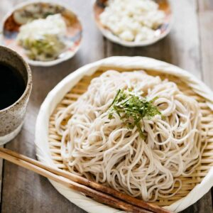 Cold soba noodles served on a bamboo strainer topped with shredded nori seaweed