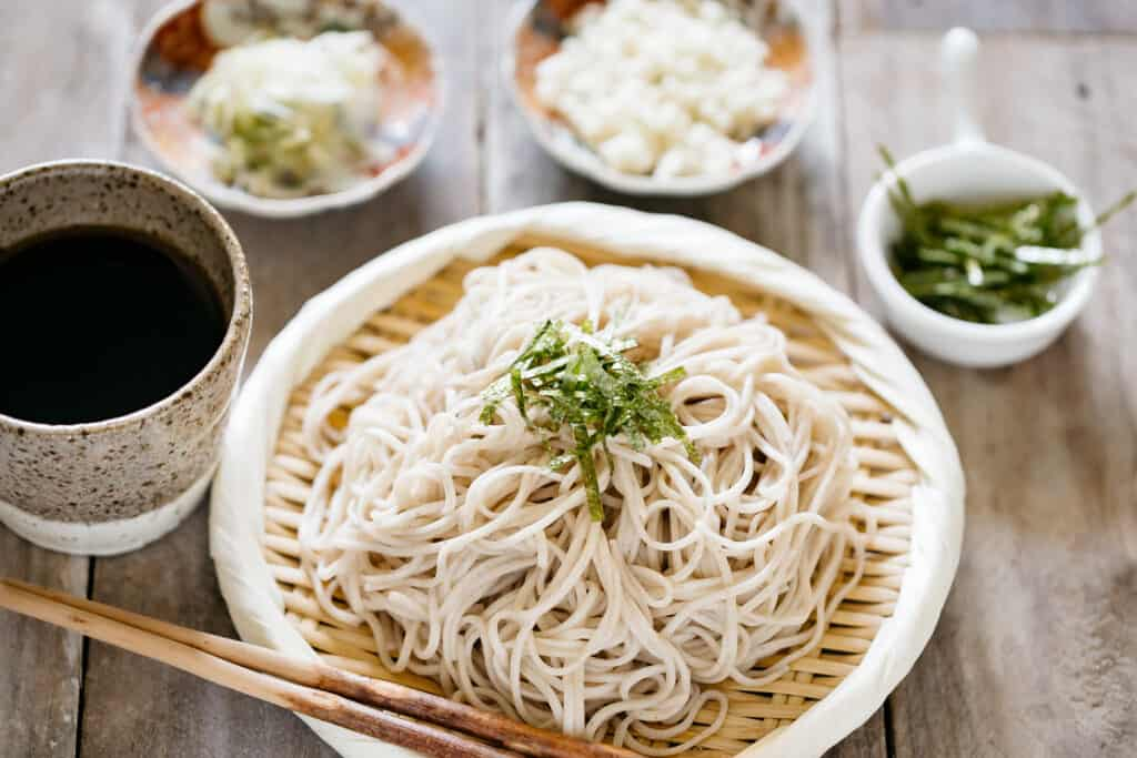 cold soba noodles served on a bamboo strainer with a bowl of dipping sauce, and condiments.