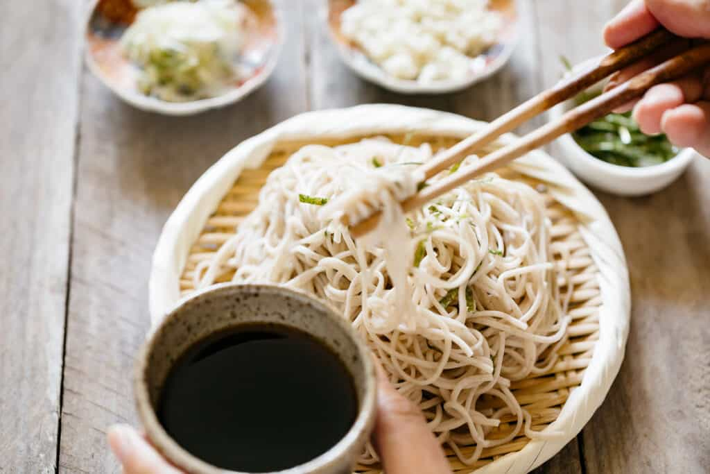 cold soba noodles served on a bamboo strainer and a pair of chopsticks holding soba noodles out dipping into a small bowl of sauce