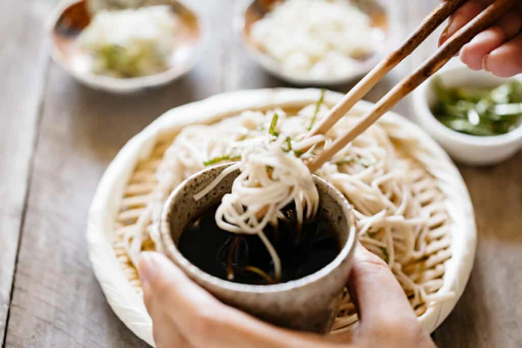 Zaru soba cold noodles dipped into a dipping sauce in a small cup