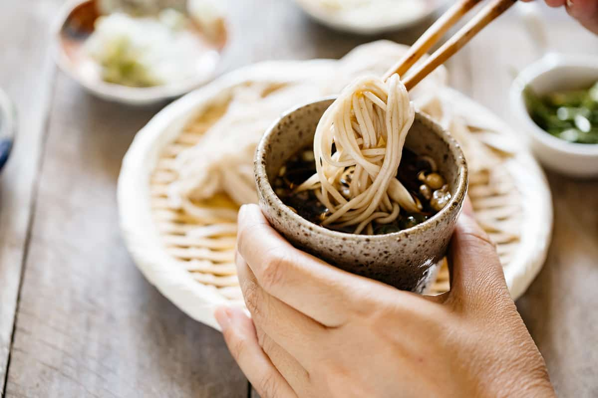 cold soba noodle dipped into a small cup of mentsuyu sauce