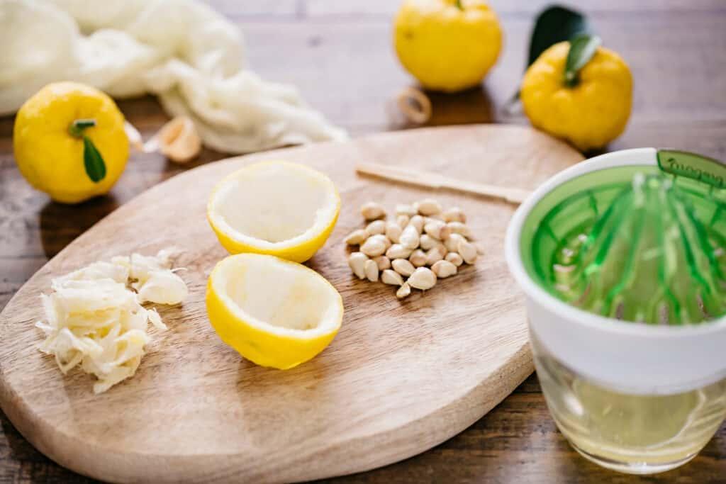 Yuzu juice in a citrus juicer, yuzu peel, seeds on an wooden board and three yuzu citrus fruits