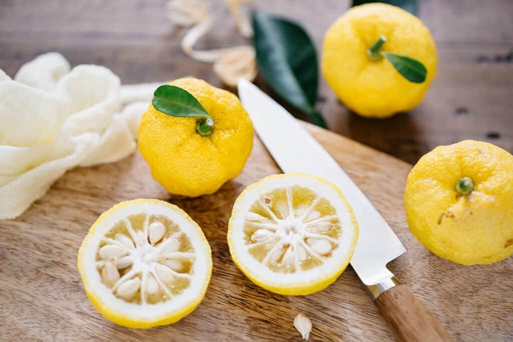 a yuzu cut in half on an wooden chopping board and three yuzu citrus with a small knife