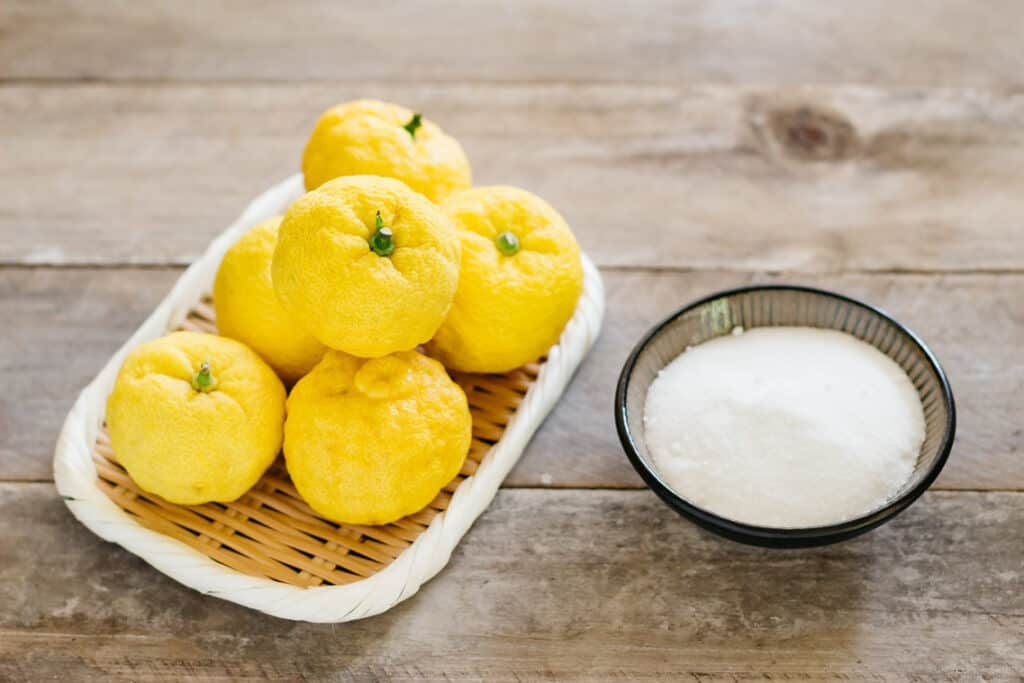 6 yuzu fruits and sugar in a small bowl