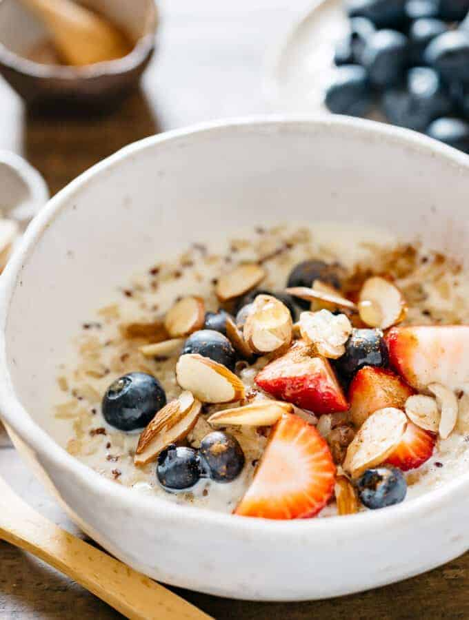 Brown rice and quinoa porridge served in a white bowl with berries and almond slices topped
