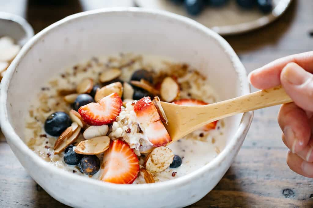 one spoonful of brown rice and quinoa porridge with berries and almond slices