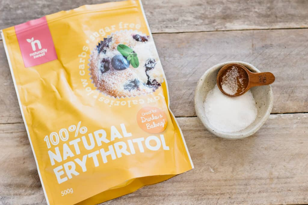natural erythritol packet and erythritol in a small bowl with a teaspoon