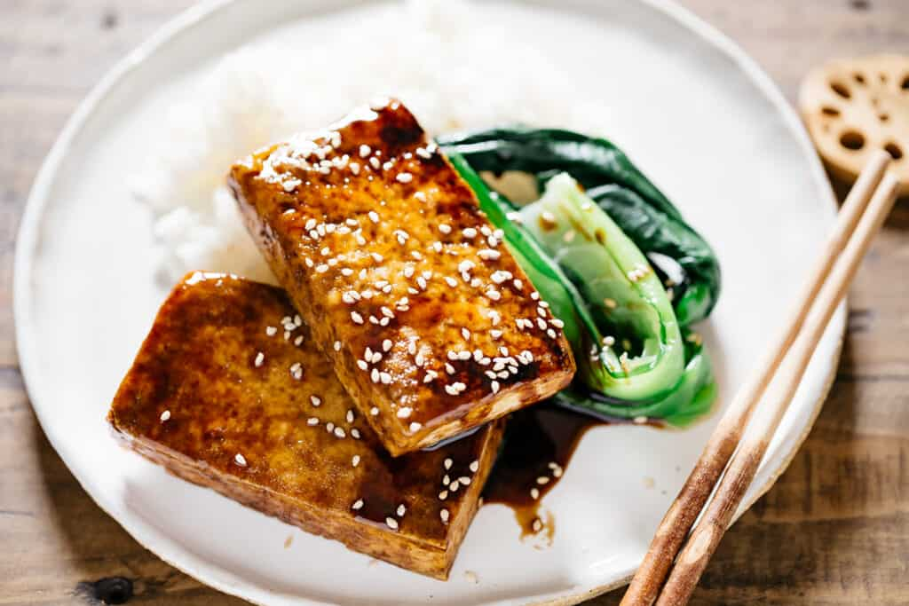 two pieces of crispy Japanese tofu steak served on bed of white rice with bok choy