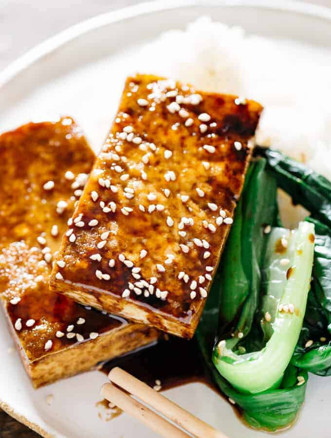 two piece of Easy crispy Japanese tofu steak served with green veggies and a plain cooked rice