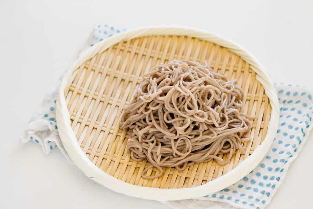 soba noodles cooked and served cold on a bamboo tray