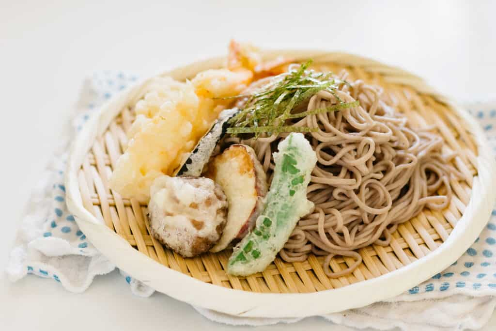 prawn tempura and vegetable tempura served on the bed of cold soba noodle