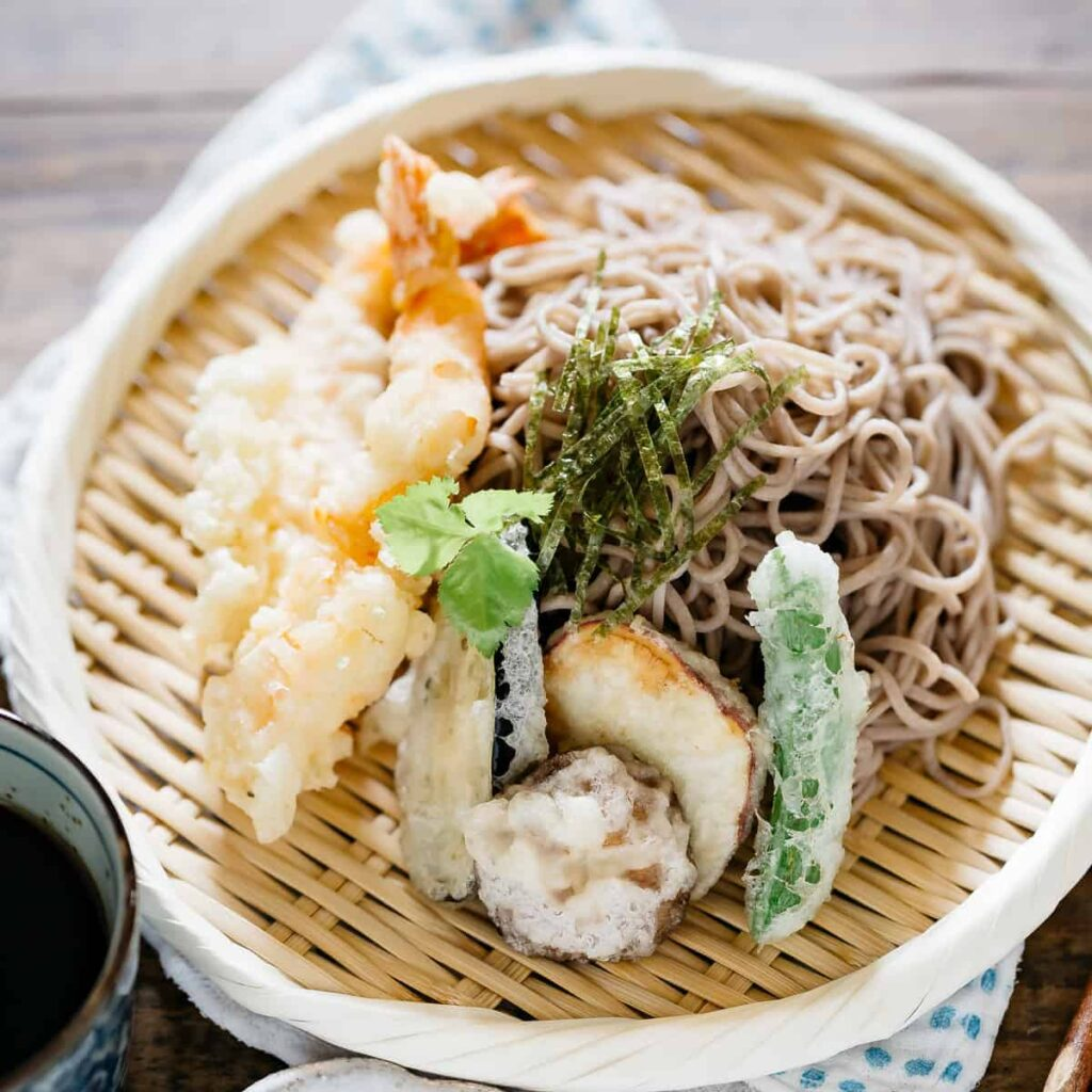 Tempura pieces and soba noodles served on a round bamboo plate