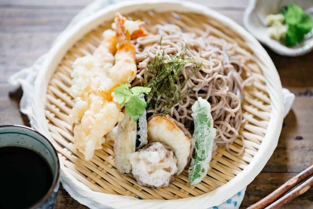 Tempura pieces and soba noodles served on a bamboo tray with dipping sauce in a small cup