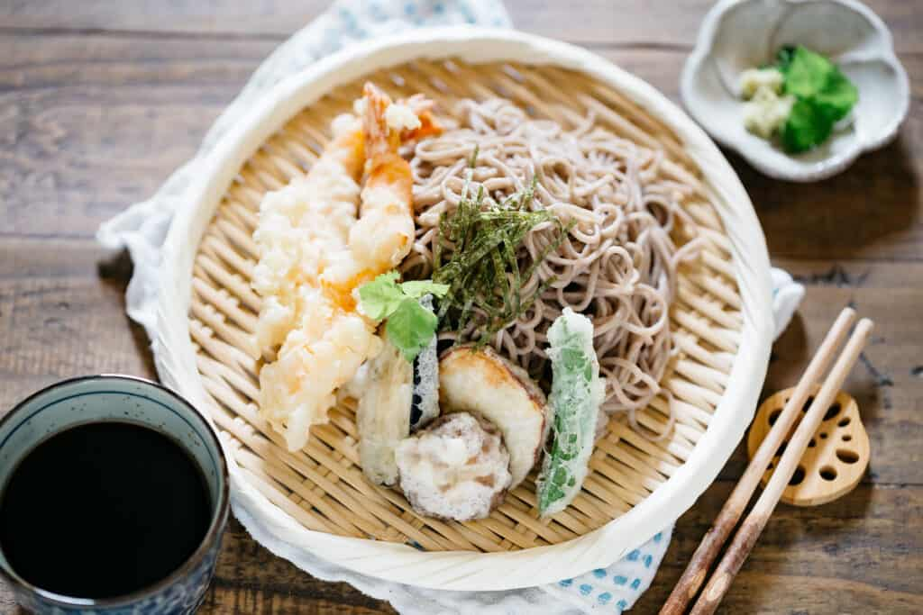 Tempura and soba noodles served together on a bamboo tray with garnish and dipping sauce in a small cup